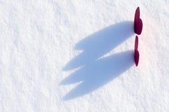 Två röda hjärtor i snö arkivfoto