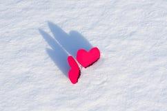 Två röda hjärtor i snö royaltyfri bild