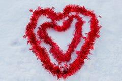 Två röda hjärtor i snön som göras av jul, binder Royaltyfria Foton