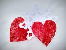 Två röda hjärtor med den vita snöflingan på snö royaltyfria foton