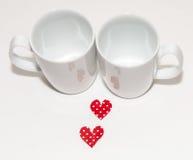 Två röda hjärtor och två vita koppar för valentindag Arkivbilder