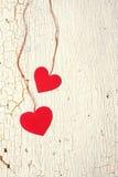 Två röda hjärtor på en träbakgrund Fotografering för Bildbyråer