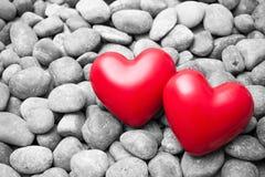 Två röda hjärtor på kiselstenstenar Royaltyfri Foto