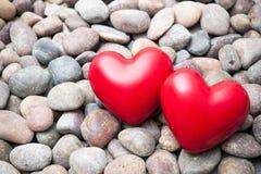 Två röda hjärtor på kiselstenstenar Arkivfoto