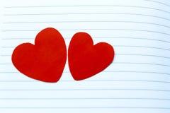Två röda hjärtor på Notebook& x27; s-sida arkivfoton