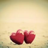 Två röda hjärtor på stranden som symboliserar förälskelse royaltyfri fotografi
