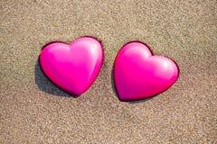 Två röda hjärtor på stranden som symboliserar förälskelse Royaltyfri Foto