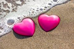 Två röda hjärtor på stranden som symboliserar förälskelse Arkivfoto