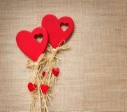 Två röda hjärtor på textilen Arkivfoto