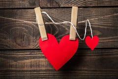 Två röda hjärtor som hänger på rep över bakgrund royaltyfria foton