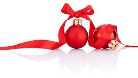 Två röda julbollar med bandet bugar på vit Royaltyfri Foto