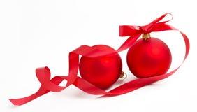 Två röda julbollar med bandet på en white Royaltyfri Bild