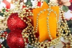 Två röda julbollar och stjärnaformstearinljus Royaltyfri Bild