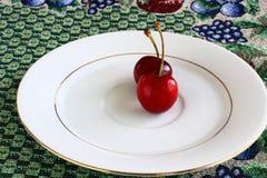 Två röda körsbär på en platta Royaltyfria Foton