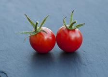 Två röda körsbärsröda tomater kritiserar på arkivfoton