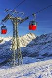 Två röda kabiner av kabeljärnväg på vintersport tillgriper i schweizare Royaltyfri Foto