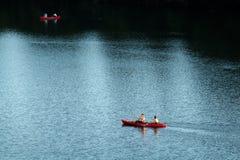 Två röda kajaker som navigerar ljust och mörkt vatten av Coloradofloden som sett från kongressbron i Austin arkivfoton