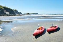 Två röda kanoter på stranden i en solig dag fotografering för bildbyråer