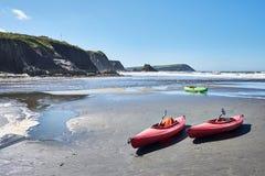 Två röda kanoter på stranden i en solig dag arkivbild