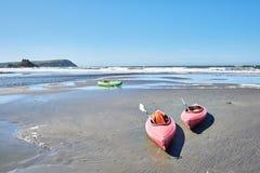 Två röda kanoter på stranden i en solig dag royaltyfri bild