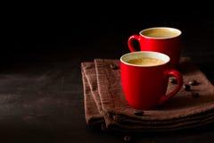 Två röda koppar av espresso på mörk träbakgrund Royaltyfria Foton