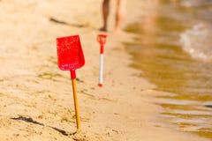 Två röda leksakskyfflar i sand på stranden Arkivfoton