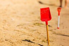 Två röda leksakskyfflar i sand på stranden Royaltyfria Foton