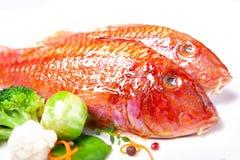 Två röda multefiskar och grönsaker royaltyfri bild