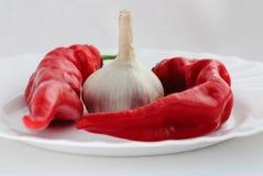 Två röda peppar och vitlök på en vit platta Arkivbild