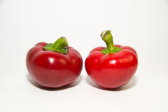 Två röda peppar på över vit Arkivbilder
