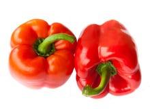 Två röda peppar som isoleras Arkivfoton