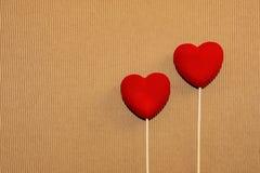 Två röda sammethjärtor på en naturlig brun paperboardyttersida St-valentin vykort för hälsningar för dag Dag för vän` s Förälskel vektor illustrationer