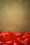 Två röda satänghjärtor på guld- bakgrunds-, valentin- eller moderdagbakgrund arkivbild