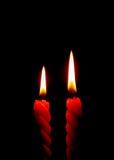 Två röda stearinljus som bränner på den svarta bakgrunden Arkivfoton