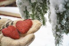 Två röda textilhjärtor och händer på tung snöig granfilialbakgrund, nära hus för röd tegelsten Glad jul, lyckligt nytt år och arkivfoton