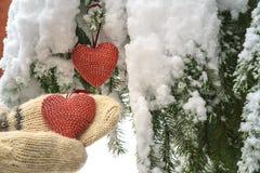 Två röda textilhjärtor och händer på tung snöig granfilialbakgrund, nära hus för röd tegelsten Glad jul, lyckligt nytt år och royaltyfria bilder