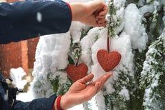 Två röda textilhjärtor och mans händer på tung snöig granfilialbakgrund, nära hus för röd tegelsten Glad jul, lycklig ny jaröst arkivfoton