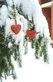 Två röda textilhjärtor som hänger på tung snöig granfilial, nära hus för röd tegelsten Glad jul, lyckligt nytt år och valentin royaltyfri foto
