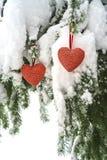 Två röda textilhjärtor som hänger på tung snöig granfilial, nära hus för röd tegelsten Glad jul, lyckligt nytt år och valentin arkivbild