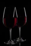 Två rött vinexponeringsglas med vin på svart bakgrund Fotografering för Bildbyråer