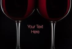 Två rött vinexponeringsglas med vin på svart bakgrund Arkivbild