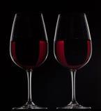 Två rött vinexponeringsglas med vin på svart bakgrund Arkivfoton