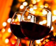 Två rött vinexponeringsglas mot träd av bokeh tänder bakgrund royaltyfri bild