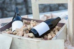 Två rött vinflaskor i gammal träask mycket med korkar arkivfoto