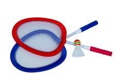 Två racket i rött och blått och en fjäderboll för badminton royaltyfri foto