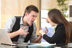 Två rasande businesspeople som argumenterar på kontoret arkivbilder