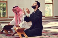 Två religiösa muslim man att be tillsammans inom moskén fotografering för bildbyråer