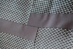 Två remsor av brunt tyg som sys till grå färger en Arkivfoto