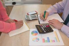 Två revisorer för affärsfolk som räknar på räknemaskininkomst för händer för avslutning för skattform royaltyfri bild