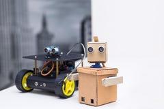Två robotar är på tabellen på ett vitt tabellhem Arkivbild